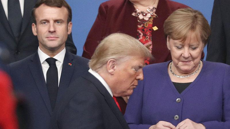 ترامب مع ماكرون وميركل خلال قمة «الناتو» حيث كان يفكر في انسحاب بلاده من الحلف.   أ.ب