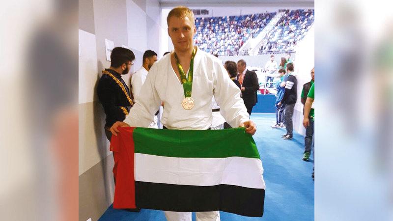 إيفان رومارنكو يرفع علم الإمارات في منافسات سابقة.  من المصدر