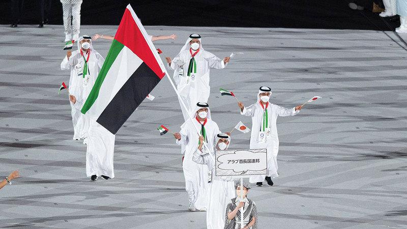السباح يوسف المطروشي حاملاً علم الإمارات خلال افتتاح دورة الألعاب الأولمبية بطوكيو أول من أمس.  من المصدر