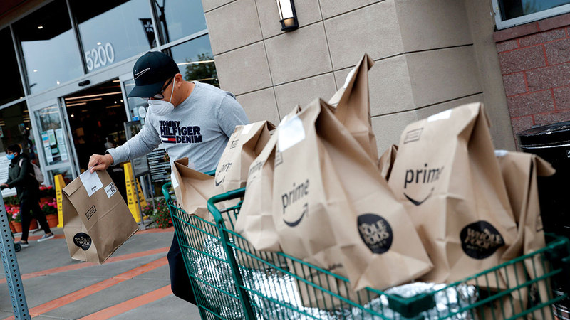أحد موظفي «أمازون» يحمل عدداً من الطرود لتسليمها.   رويترز