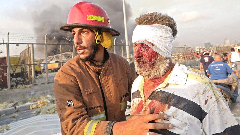 رجل إطفاء يساعد أحد الجرحى بعد إسعافه في موقع الانفجار.   أ.ف.ب