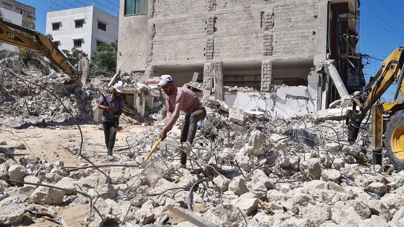 عمال خلال البحث عن حديد التسليح بين الركام.    الإمارات اليوم