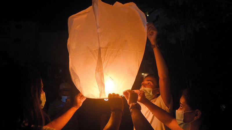 يطلقون المصابيح الورقية ليلة إحياء الذكرى الأليمة.  إي.بي.إيه