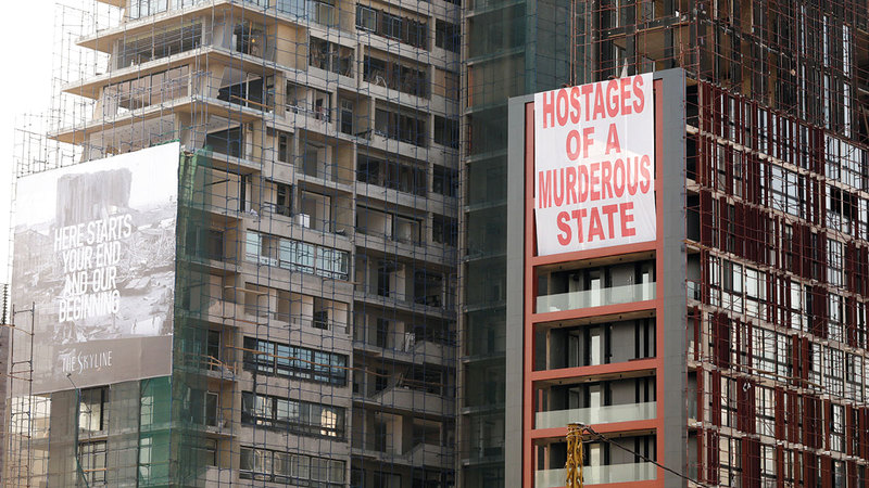 بعض المباني التي توقف فيها العمل بعد انفجار المرفأ، وقد علقت عليها لافتات كتب عليها «رهائن دولة قاتلة»، «هنا تبدأ نهايتك وبدايتنا» في ذكرى مرور عام على الكارثة.  رويترز