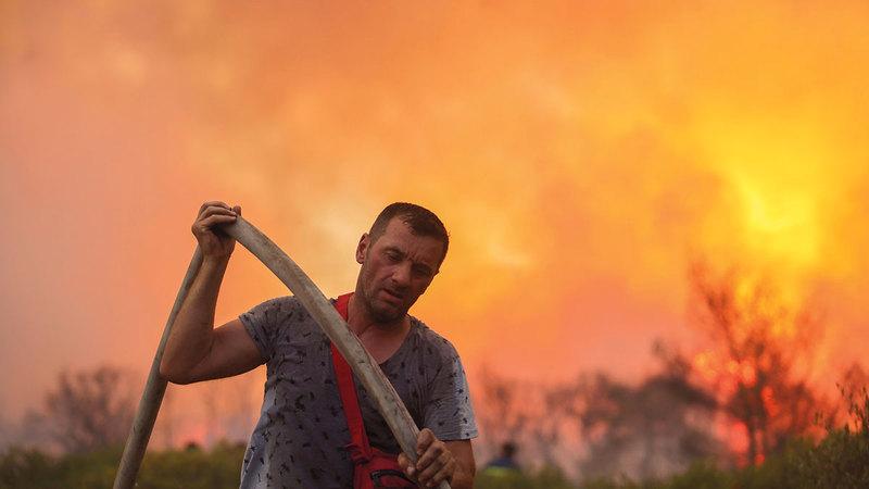 رجل إطفاء متطوع يحمل خرطوم مياه أثناء مكافحة النيران في فاربوبي.  رويترز