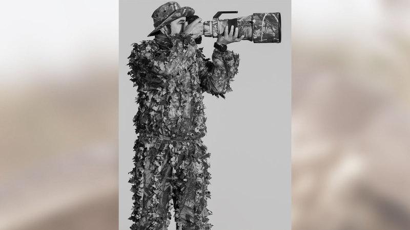 الحمادي في ملابس مموّهة يتربص لالتقاط صورة من صوره النادرة.  من المصدر