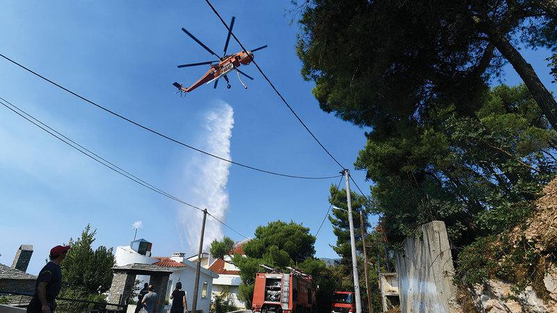 مروحية تحاول إطفاء النيران المشتعلة شمال العاصمة أثينا.   أ.ب