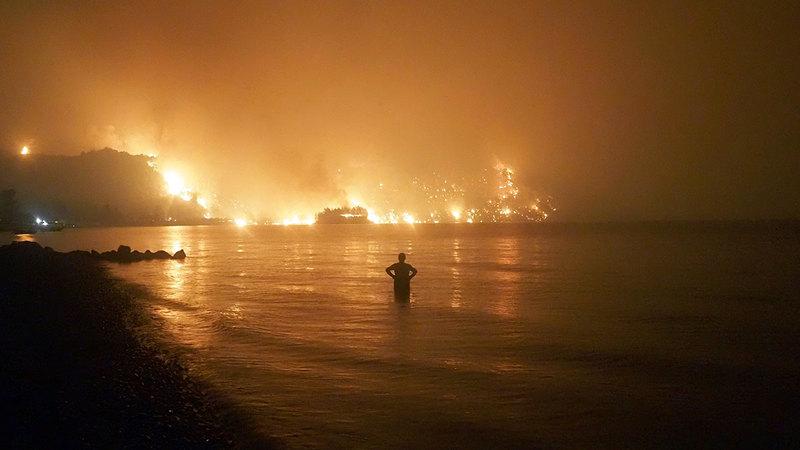 رجل يراقب ألسنة اللهب وهي تقترب من شواطئ كوشلي بالقرب من قرية ليمني فوق جزيرة إيفيا على بعد 160 كيلومتراً من العاصمة أثينا.   أ.ب
