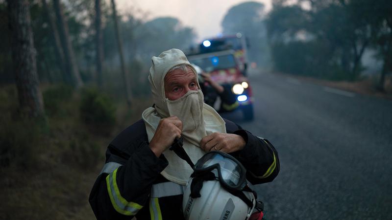 رجل إطفاء يستعد للاقتراب من النيران لإخمادها.  أب