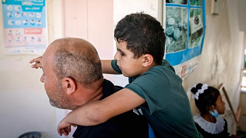 الأب يحمل ابنه ليُجلسه على مقعد الدراسة.  أ.ف.ب