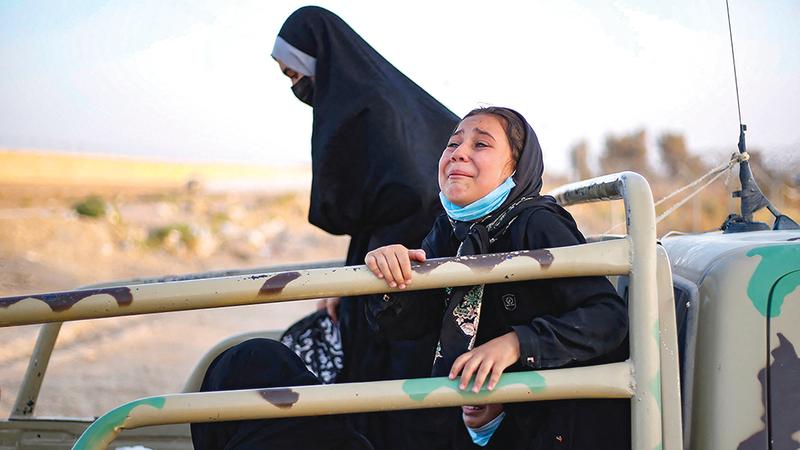 نساء وأطفال يبكون حزناً وخوفاً داخل شاحنة بعد أن أجبروا على ترك منازلهم بحثاً عن مكان أكثر أمناً.  أ.ف.ب