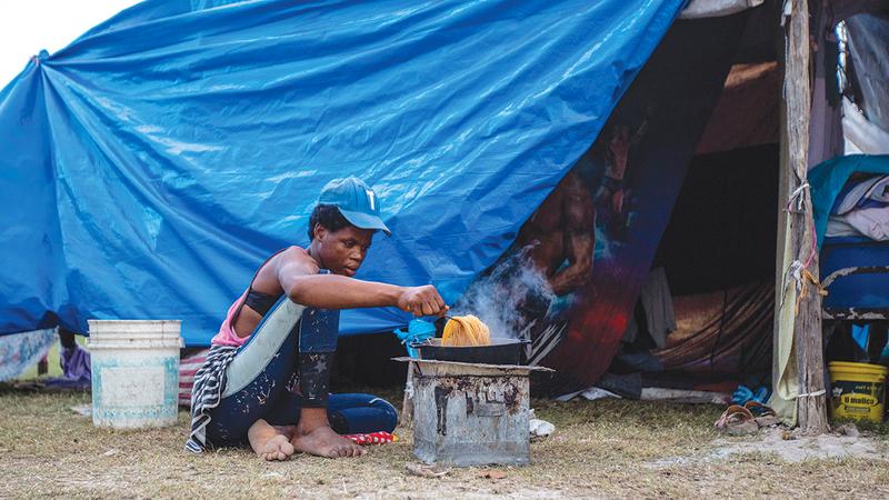 يطبخ المعكرونة وهو يفترش الأرض خارج خيمته المؤقتة.   رويترز