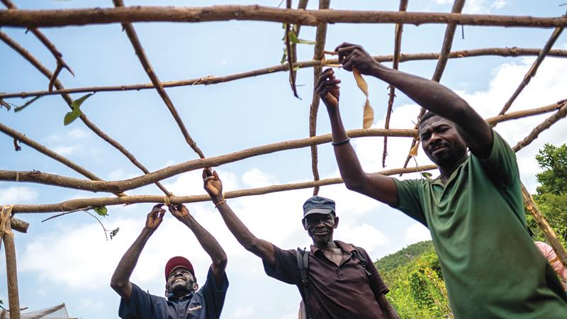 3 رجال يبنون كوخاً مؤقتاً لإيوائهم داخل المخيم.   رويترز