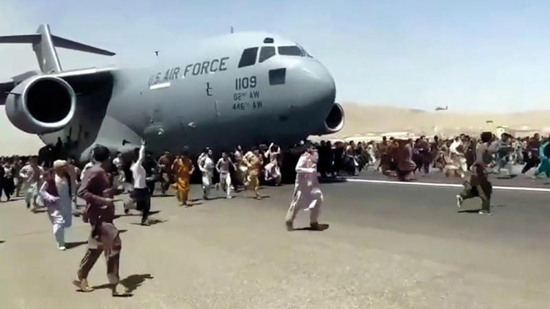 حشد من الأفغان يحاولون استقلال طائرة حربية أميركية في مطار كابول.  من المصدر