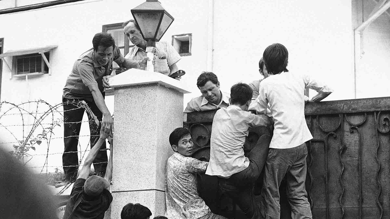 فيتناميون جنوبيون يتسلقون جدار السفارة الأميركية بسايغون في محاولة يائسة للهروب.  من المصدر