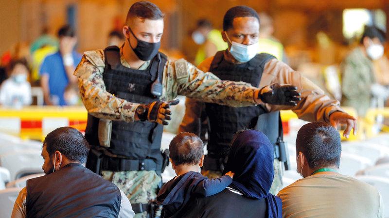 رجال المارينز مع مجموعة من المواطنين الأفغان بعد أن تم إجلاؤهم من كابول.   رويترز