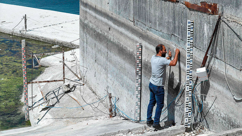 فني يقيس منسوب المياه على طول جدار سد «تشرين».   أ.ف.ب