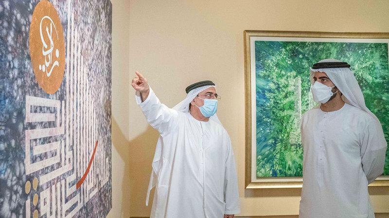 سالم القاسمي تجوّل في أروقة المعرض واستمع لشرح من مندي حول الأعمال.  من المصدر