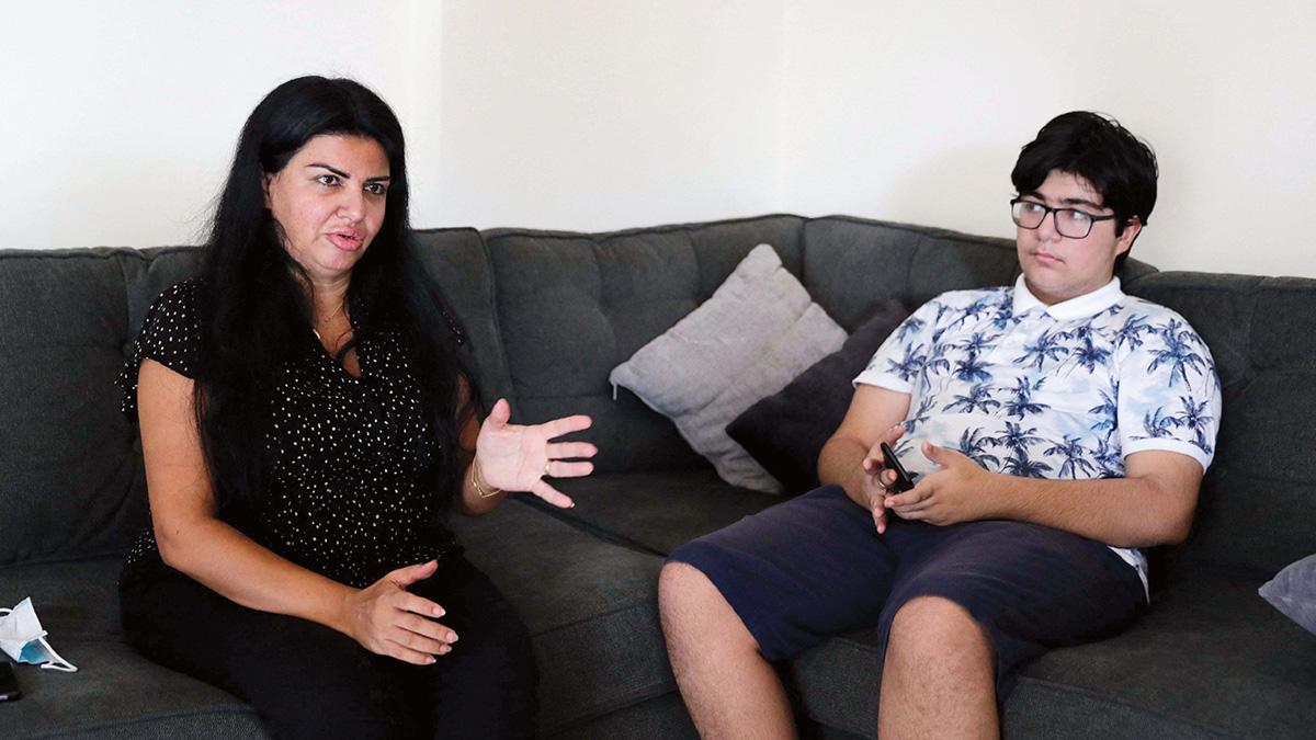 رولا مراد برفقة ابنها «ريان» الذي تنوي إلحاقه بمدرسة حكومية مثل أخيه بعد تراجع إمكانات العائلة. . أ.ف.ب