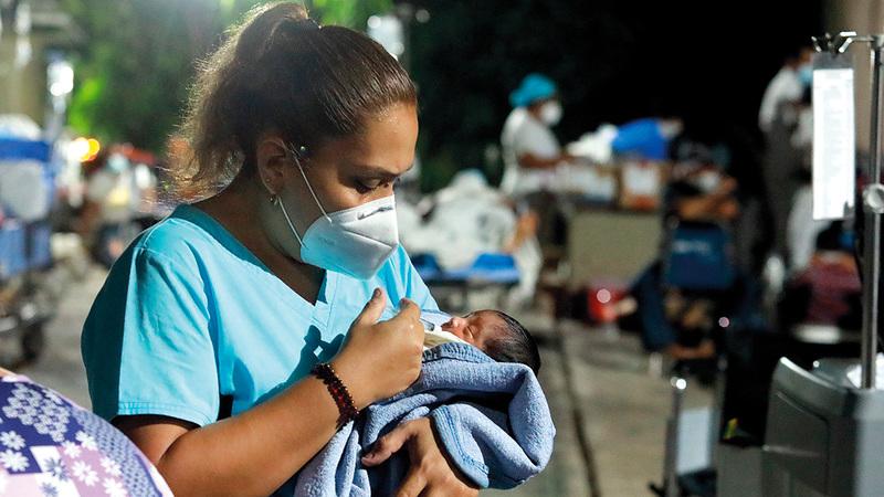 ممرضة تعتني بطفل بعد أن تم إجلاء جميع المرضى من مستشفى في المنطقة التي ضربها الزلزال. إي.بي.إيه