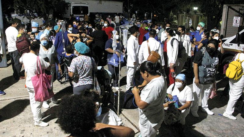الأطباء والمرضى في الشارع بعد إجلائهم من مستشفى في المنطقة التي ضربها الزلزال.  رويترز