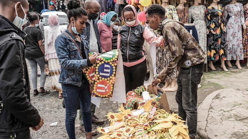مشترون يلتفون حول بائع ديكور منزلي استعداداً للعام الإثيوبي الجديد.  أ.ف.ب
