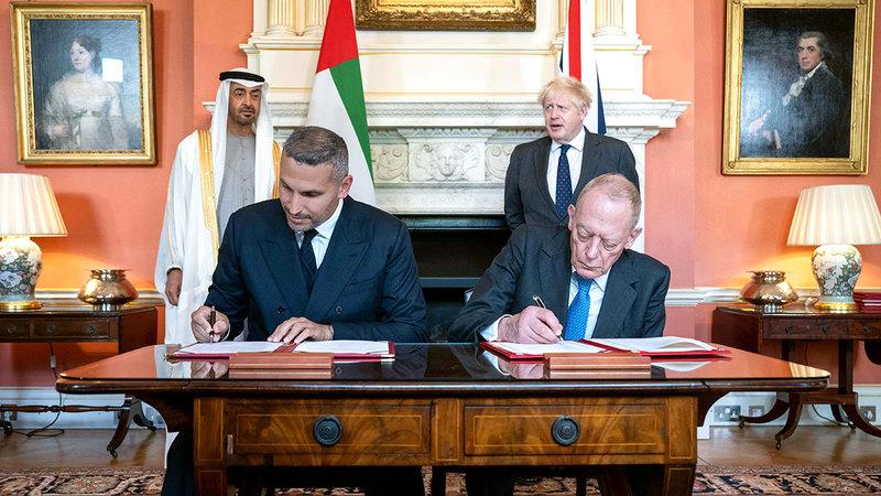 محمد بن زايد ورئيس وزراء بريطانيا يشهدان توقيع الاتفاقية.  وام