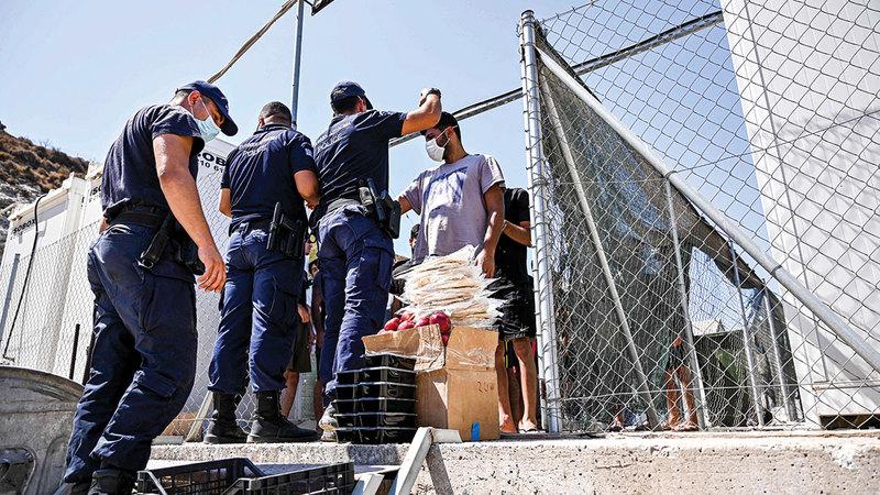 الشرطة اليونانية توزّع الطعام على طالبي لجوء جدد.    أ.ف.ب