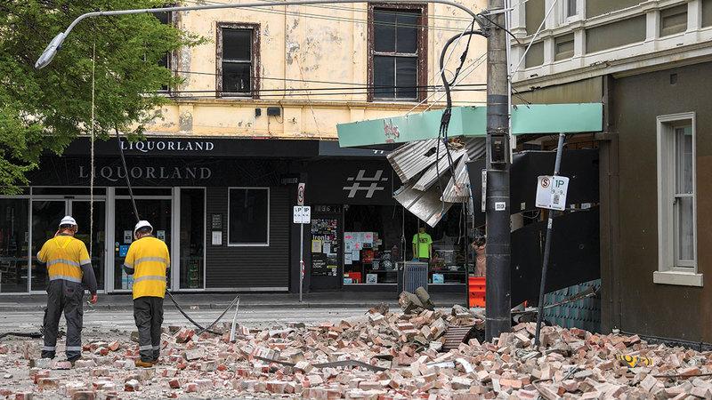 عمال الإنقاذ يتفقدون آثار الدمار في مدينة ملبورن.  أ.ب