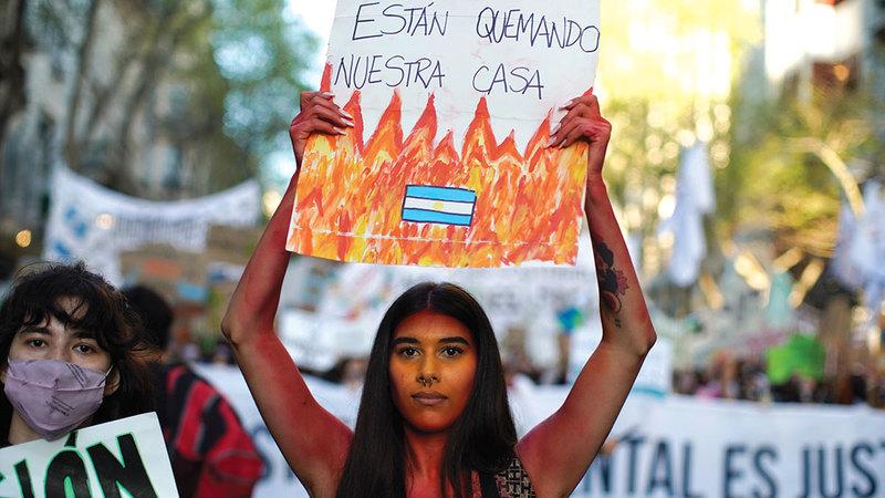 فتاة تحمل لافتة بالإسبانية في تظاهرة بشأن المناخ في الأرجنتين كتب عليها «إنهم يحرقون منازلنا».  أ.ب