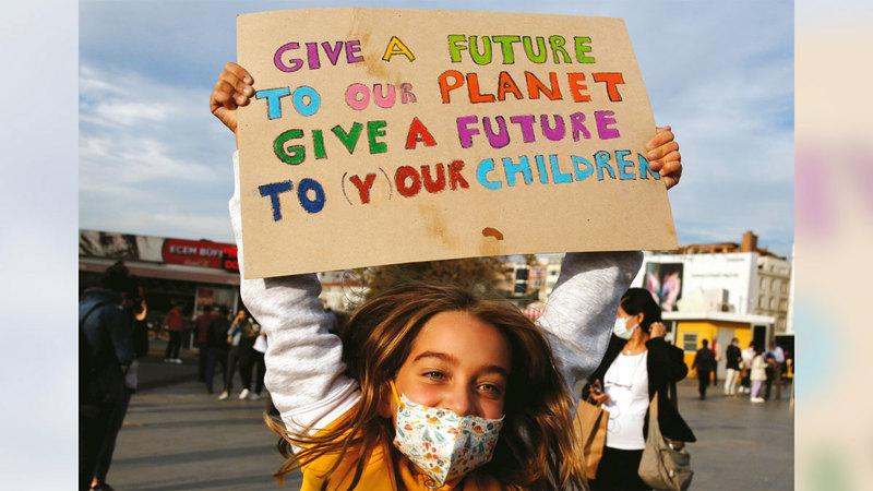 فتاة تركية تحمل لافتة عليها عبارات «امنحوا مستقبلاً لكوكبنا.. امنحوا مستقبلاً لأطفالنا».  رويترز