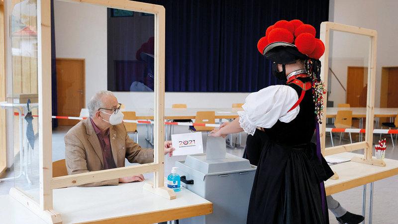 امرأة في زي تقليدي تدلي بصوتها في أحد مراكز الانتخابات.   إي.بي.إيه