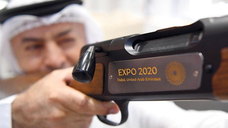 خميس حمر العين مستعرضاً بندقية تحمل شعار «إكسبو 2020».   تصوير: إريك أرازاس