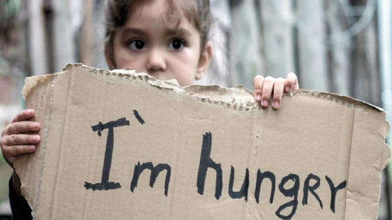 فتاة أميركية ترفع لافتة كتب عليها «أعاني الجوع».  أرشيفية