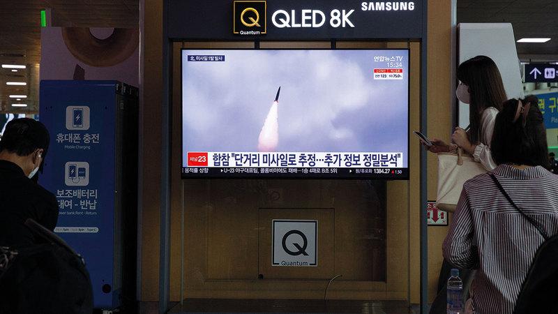 كوريون شماليون يشاهدون إطلاق الصاروخ في التلفزيون خلال نشرة الأخبار.     إي.بي.إيه
