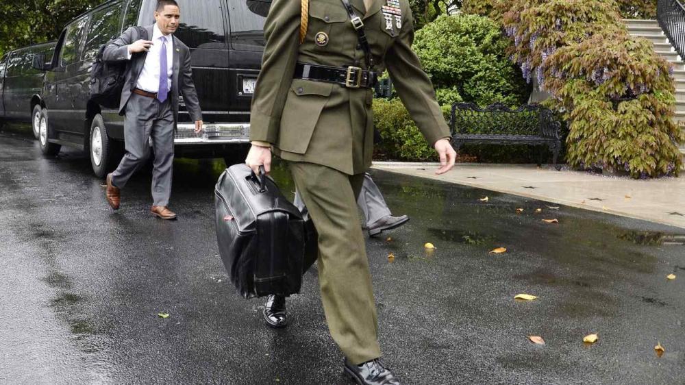 مساعد عسكري يحمل الحقيبة النووية في حديقة البيت الأبيض.  من المصدر