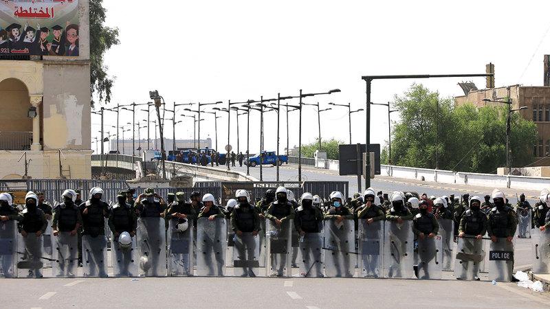 قوات مكافحة الشغب تغلق طريقاً رئيساً في العاصمة بغداد.   إي.بي.إيه