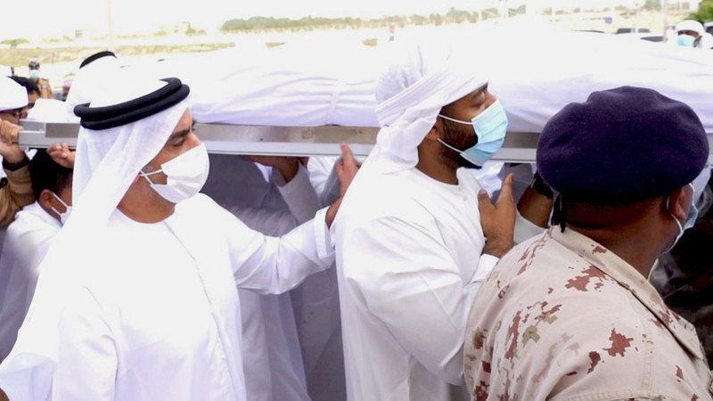 سيف بن زايد خلال مشاركته في تشييع جثمان شهيد الواجب خميس الهولي.   وام
