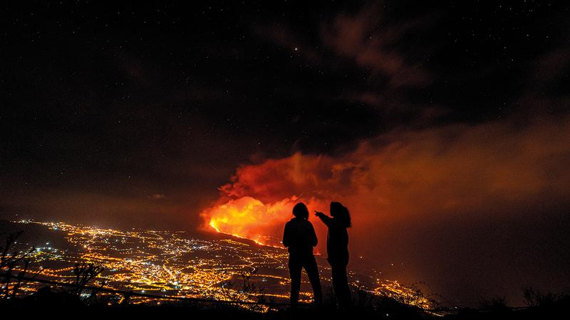 امرأتان تنظران إلى البركان من مسافة بعيدة.   إي بي إيه