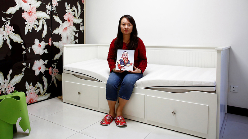 داي شياولي تحمل صورة ابنتها التي أُخذت منها.  أرشيفية