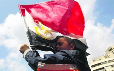 طفل يحتضن علم مصر في ميدان التحرير أثناء الاحتجاجات الشعبية.   رويترز
