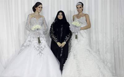 منى المنصوري مع عارضتين ترتديان تصميميها لفستان العروس.تصوير: إريك أرازاس