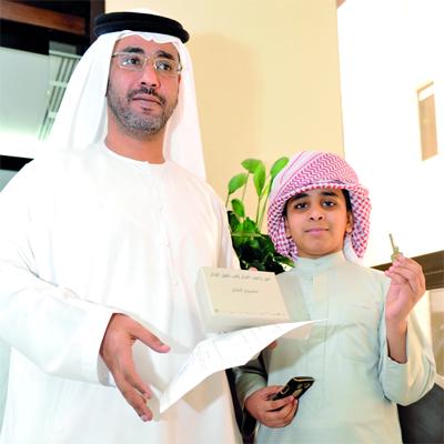 """مواطن وابنه يتسلمان مفتاح فيلا في """" مشروع الفلاح """".  الإمارات اليوم"""