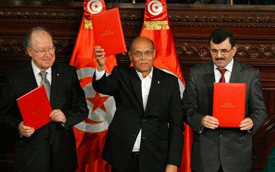 رئيس تونس يتوسط مصطفى بن جعفر (يسار) بعد التوقيع على الدستور الجديد ..رويترز