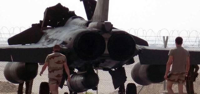 موظفان من الدعم العسكري الفرنسي يسيران نحو طائرة مقاتلة من طراز «رافال» تتهيأ لتوجيه ضربة لـ«داعش» في العراق. أ.ف.ب