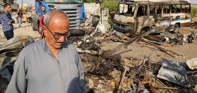 مدنيون يتفقدون موقع انفجار سيارة مفخّخة في حي المشتل شرق بغداد.  أ.ب