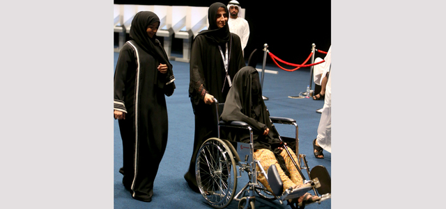 متطوعة تساعد امرأة مسنّة على كرسي متحرك للإدلاء بصوتها. تصوير: نجيب محمد
