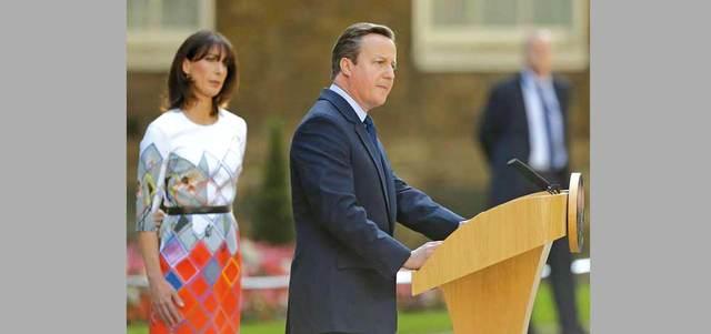 كاميرون يتحدث للصحافيين أمام مقر إقامته في داونينغ ستريت وخلفه زوجته سامانثا. أ.ب