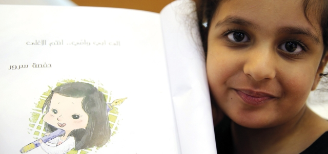 حفصة تحمل قصصها في معرض الشارقة. من المصدر