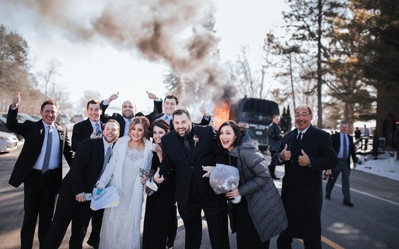 عروسان يلتقاطان صوراً تذكارية مع حافلة زفافهما المحترقة